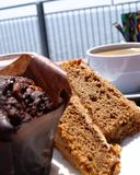 Coffee and Cake. Chocolate muffin, cake and a cup of coffee on an outdoor cafe table Stock Photo