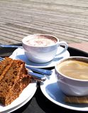 Coffee and cake Break. Cups of Cappucino and coffee with cake at an outdoor cafe stock photo