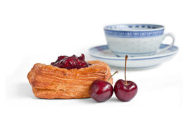 Coffee cake with cherry and a cup Stock Image