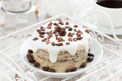 Coffee cake with icing decorated with cocoa beans on a plate Stock Image