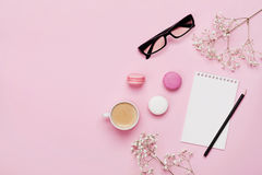 Coffee, cake macaron, notebook, eyeglasses and flower on pink table from above. Female working desk. Cozy breakfast. Flat lay.