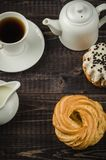 Coffee with cake and milk/breakfast: coffee with cake and milk on a dark wooden background. Top view. Dessert biscuit pastries cupcake white teapot creamer stock images