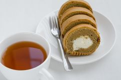 Coffee Cake Roll with a Cup of Tea. Coffee cake roll with a cup of tea on tea breaking time Stock Images