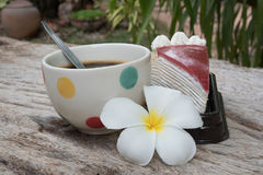 Coffee and cake. Strawberry cake  Coffee cup and Frangipani Flower on the wooden table Royalty Free Stock Photography