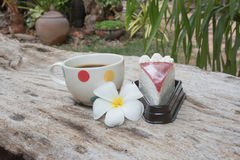 Coffee and cake. Strawberry cake  Coffee cup and Frangipani Flower on the wooden table Royalty Free Stock Images