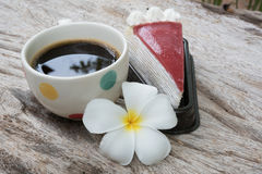 Coffee and cake. Strawberry cake  Coffee cup and Frangipani Flower on the wooden table Royalty Free Stock Photo