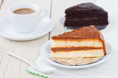 Coffee cake on white plate on wooden table with coffee and choco Royalty Free Stock Images