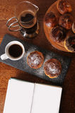 Coffee and cakes are served on a wooden table and slate tray. Open book with free place for text Royalty Free Stock Image