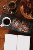 Coffee and cakes are served on a wooden table and slate tray. Open book with free place for text Stock Photos
