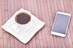 Coffee call. Cup of coffee next to smart phone on a wooden background Royalty Free Stock Images