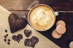 Coffee cappuccino with beautiful foam next macarons and chocolate heart. Stock Photos