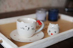 Coffee cappuccino in cute cup in the shape of cat. On a wooden tray. Candles on the background Royalty Free Stock Photo