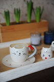 Coffee cappuccino in cute cup in the shape of cat. On a wooden tray. Candles on the background Stock Images