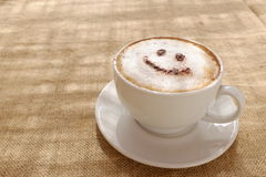 Coffee cappuccino with foam or chocolate smiling welcome happy face Stock Image