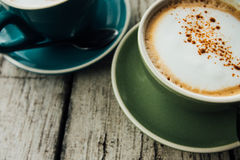 Coffee cappuccino in a green cup on a saucer. Two cups coffee on a wooden table Stock Images