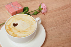 Coffee cappuccino in a white cup. A box with a gift and a rose. Royalty Free Stock Photography