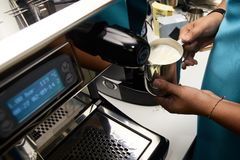 Coffee cappuccino. Work barista. Preparation of drink. Mans hand. Whute milk royalty free stock images