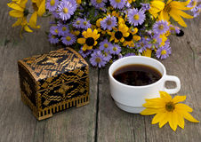 Coffee, casket and bouquet of beautiful wild flowers, on a woode Royalty Free Stock Photo