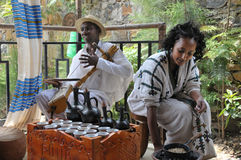 Coffee ceremony. Axum, Ethiopia - September 28, 2012: Young Ethiopian woman in traditional clothing is preparing a traditional coffee ceremony. Man is playing on Stock Image