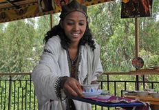 Coffee ceremony. Axum, Ethiopia - September 28, 2012: Young Ethiopian woman in traditional clothing is serving coffee during a traditional coffee ceremony. This Stock Photos