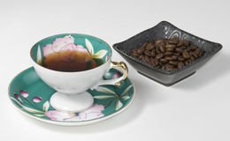 Coffee in china cup. Antique cup with coffee and a dish of beans Stock Image