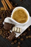 Coffee and chocolate. Cup of coffee with chocolate candies, coffee beans and cinnamon sticks Stock Image