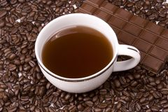 Coffee And Chocolate. Coffee in white mug on coffee beans with chocolate bar Stock Photography