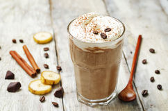 Coffee chocolate banana smoothie with coconut whipped cream. Toning. selective focus royalty free stock photography
