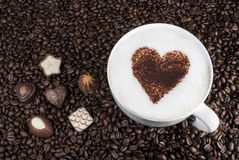 Coffee and Chocolate Bliss. Coffee in a white mug with a cinnamon heart surrounded by coffee beans and chocolate Stock Photos