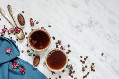 Coffee, chocolate and blue napkin. Morning composition with a cup of black coffee, chocolate candies and blue linen napkin on a marble surface with space for royalty free stock images