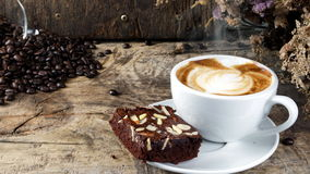 Coffee and Chocolate Brownie. Put on a wood table with dark roasted coffee beans Royalty Free Stock Images