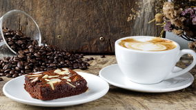 Coffee and Chocolate Brownie. Put on a wood table with dark roasted coffee beans Stock Photos