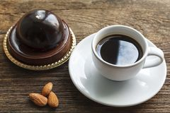 Coffee with chocolate cake and almonds on wood background Royalty Free Stock Photos