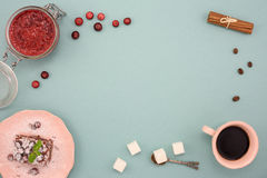 Coffee and chocolate cake with cranberry jam and cinnamon on wooden board, over turquoise background. Top view, copy space. Royalty Free Stock Image