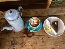 Coffee and chocolate cake. Latte art. Bali. Latte coffee and in turquoise cup and saucer with raw chocolate cake, metal tea pot on wooden table. A latte is a royalty free stock photos