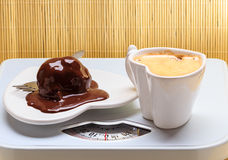Coffee and chocolate cake on weighing scale. Royalty Free Stock Images