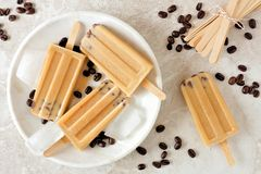 Coffee and chocolate chip popsicles above view on marble. Coffee and chocolate popsicles above view in white plate against a marble background Stock Photo