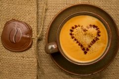 Coffee with chocolate heart. Cup of coffee with chocolate heart on textured box with bean wax seal stock photo