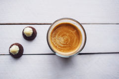 Coffee and chocolate on the white table. Two chocolates candies and cup of espresso on the white wooden table. Top view. Place for text Royalty Free Stock Images