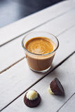 Coffee and chocolate on the white table. Two chocolates candies and cup of espresso on the white wooden table. Top view. Place for text Stock Images