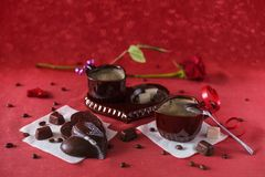 Coffee with chocolate for your beloved on Valentine`s Day. On the red tablecloth is a service in the form of hearts. Coffee is poured into the cups. On napkins Stock Image