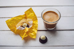Coffee and chocolates in the white wooden table. Two chocolates candies and cup of espresso on the white wooden table. Top view. Place for text Stock Photography