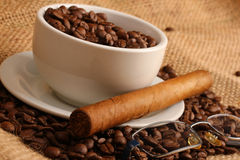 Coffee and cigar. Coffee beans in white cup with cuban cigar and glasses stock images