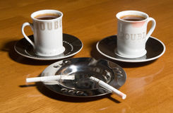 Coffee and cigarettes. Two cups of coffee and two cigarettes on a table Stock Photo