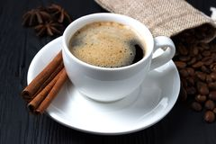 Coffee with cinnamon and anise on a black background and a bag of coffee beans Royalty Free Stock Photography