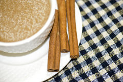 Coffee and cinnamon. A cup of coffee and cinnamon on a checkered sheet Stock Image