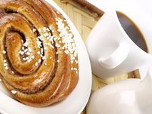 Coffee and Cinnamon Roll. On a plate Royalty Free Stock Images