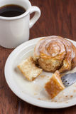 Coffee and Cinnamon Roll. Coffee and a Cinnamon Roll on a wooden table Stock Image