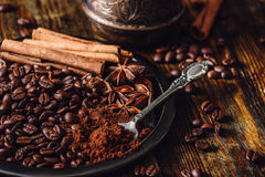 Coffee with Cinnamon and Star Anise. Coffee Beans with Spooonful of Ground Coffee, Cinnamon Sticks and Chinese Star Anise on Metal Plate. Some Beans Scattered Stock Images