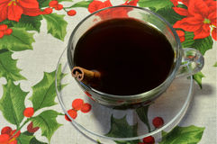 Coffee with cinnamon stick in the transparent cup on Christmas napkin with red flowers Stock Images